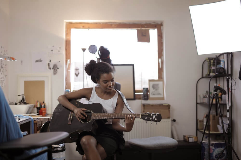 black lady learning acoustic guitar