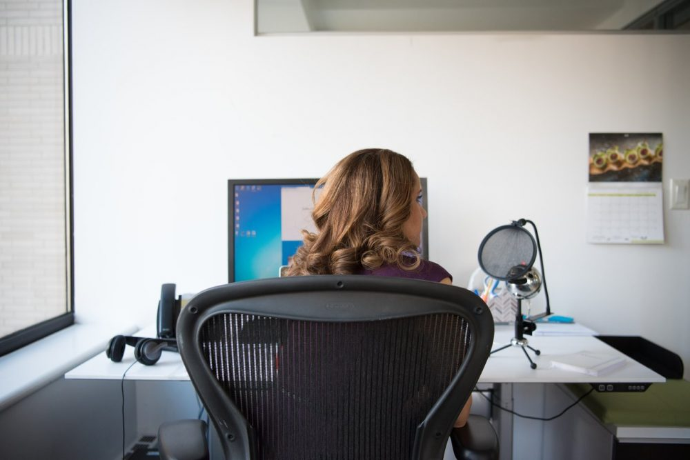 woman-siting-on-chair-in-front-of-turn-on-computer-monitor